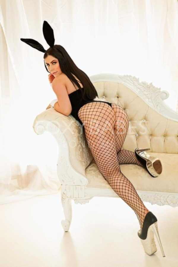 sexy brunette in bunny ears headband slouched on chair