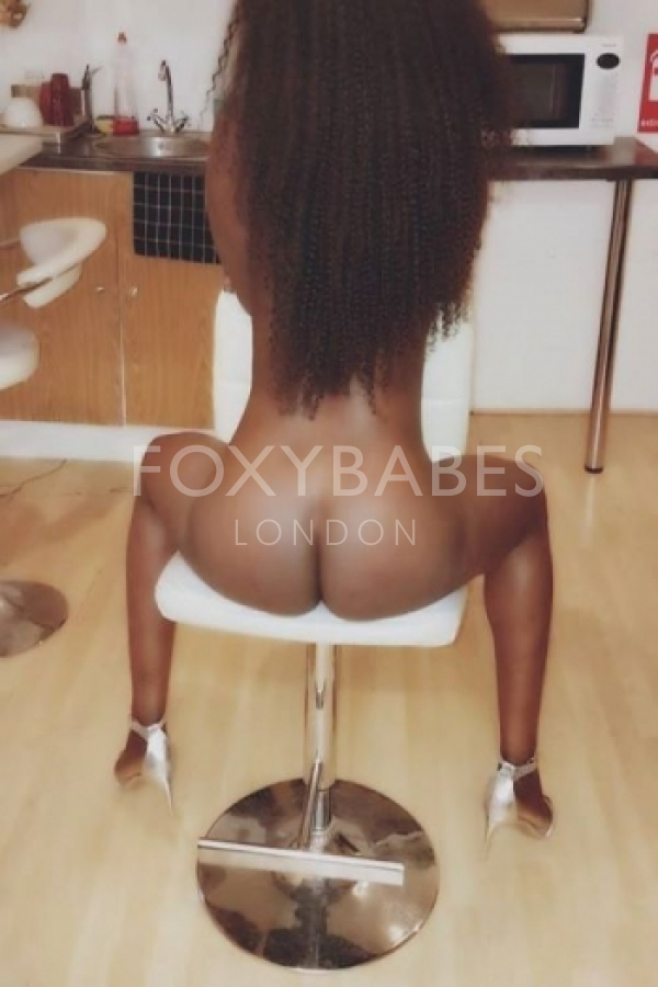 ebony escort naked, sat on chair