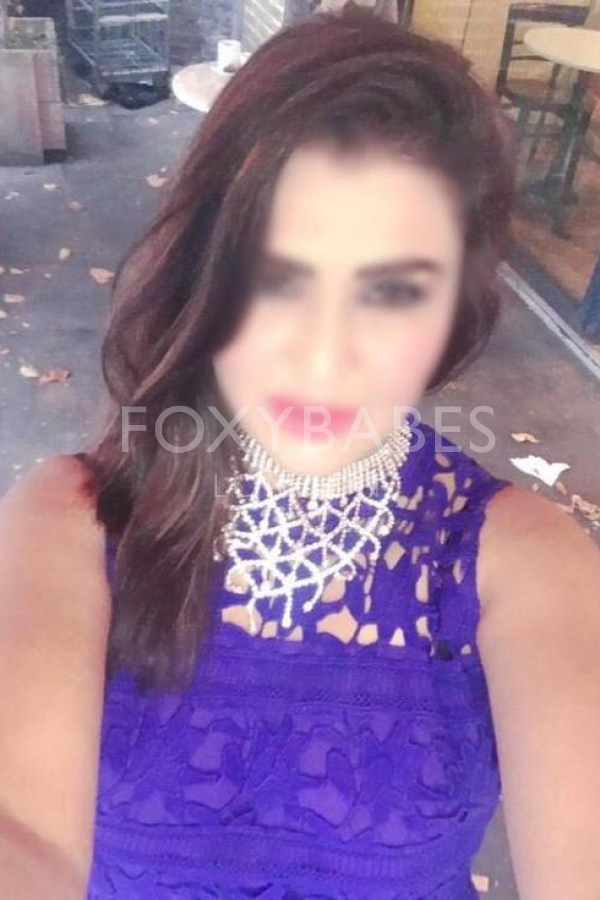 Aesha in blue dress taking selfie